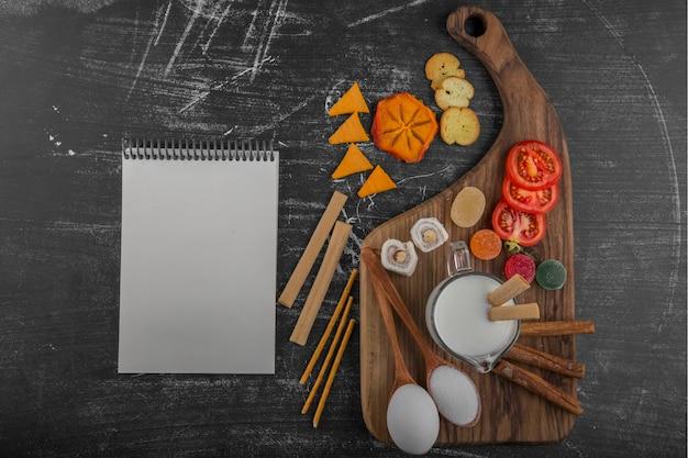 Planche à collation avec des craquelins et des légumes avec un livre de cuisine de côté