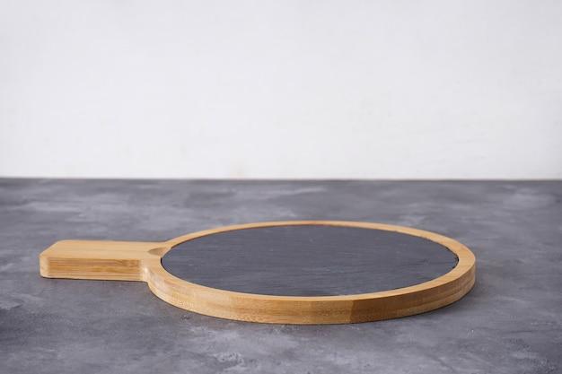 Planche de cuisine en bois sur fond gris, espace pour le texte.