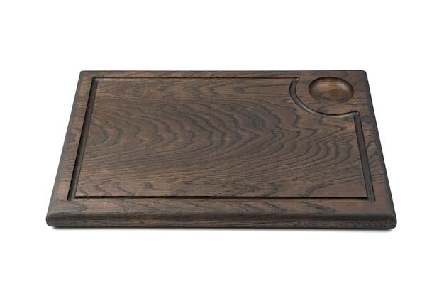 La planche de cuisson est brun foncé sur fond blanc. vue de côté. le concept de cuisine.
