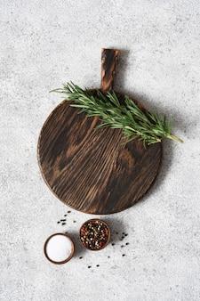 Planche à découper au romarin et épices sur un fond de béton clair.