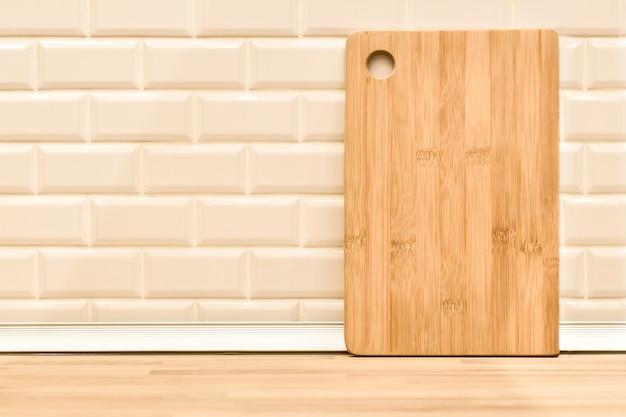Planche à découper en bois de bambou contre un mur de briques blanches et un fond de table de cuisine. intérieur clair