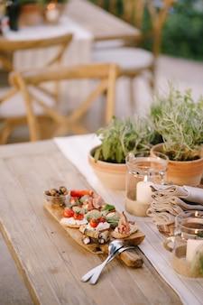 Planche à découper en bois avec de la charcuterie et des couverts sur la table par les fleurs dans les pots