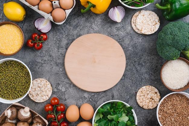 Planche à découper en bois circulaire entourée de légumes frais et d'oeufs sur fond de béton