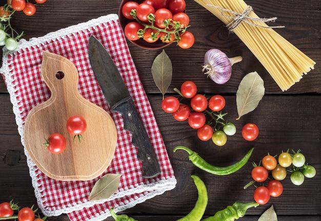Planche à découper en bois avec un couteau et tomates cerises rouges fraîches
