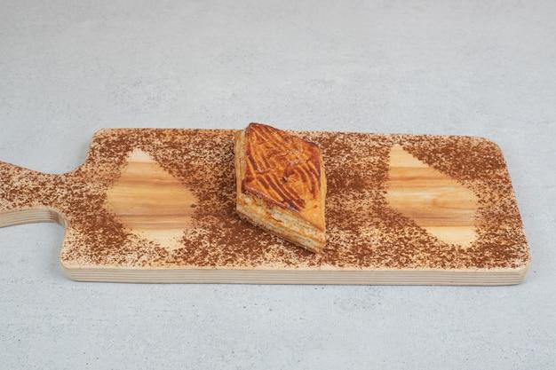 Une planche à découper en bois avec du cacao en poudre et des biscuits