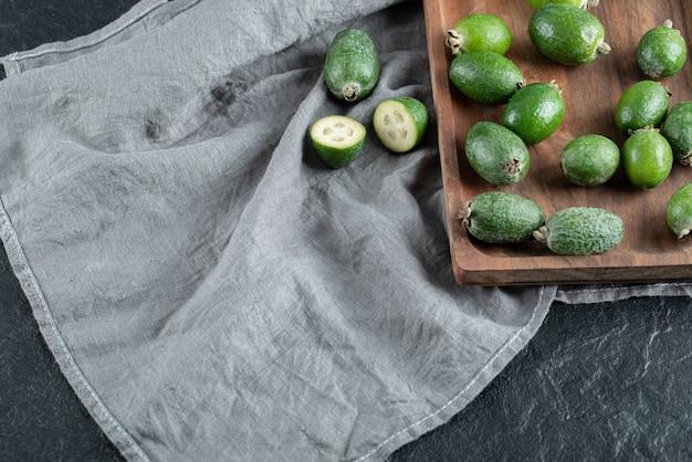 Une planche à découper en bois avec du feijoa frais.