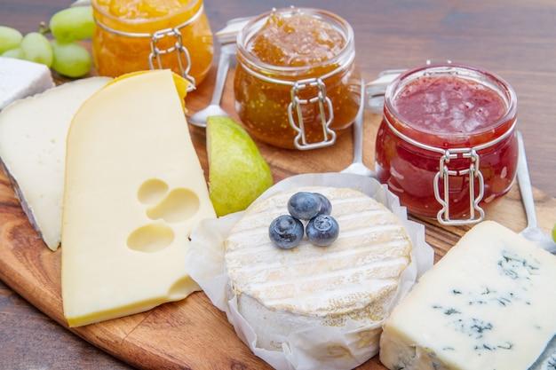 Planche à découper en bois avec du fromage et des confitures