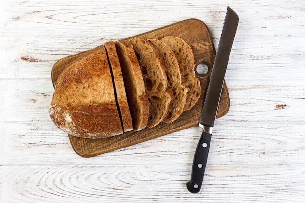 Planche à découper en bois avec du pain blanc en tranches et un couteau sur une table en bois