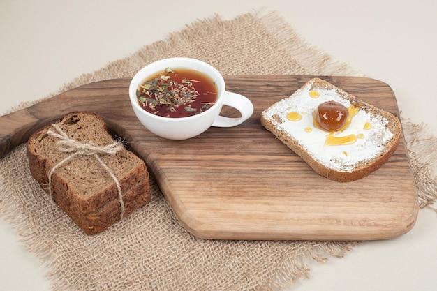 Une planche à découper en bois avec du pain grillé et une tasse de thé sur un sac.