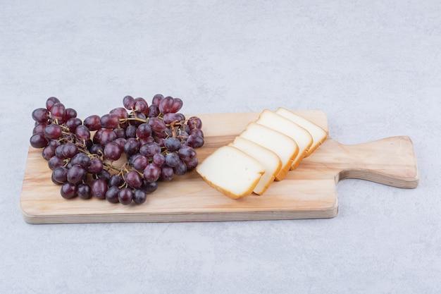 Une planche à découper en bois avec du pain tranché et des raisins. photo de haute qualité