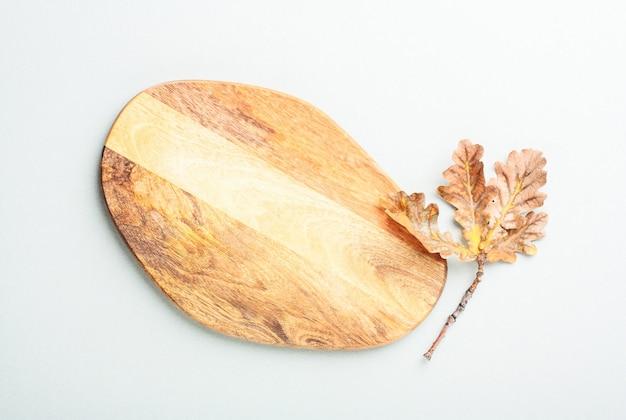 Planche à découper en bois et feuille de chêne séchée sur fond gris