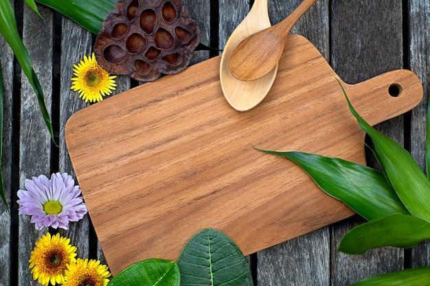 Planche à découper en bois avec des feuilles vertes tropicales, des fleurs roses et jaunes et une cuillère
