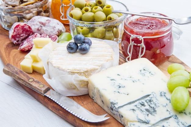 Planche à découper en bois avec fromage, charcuterie et confitures