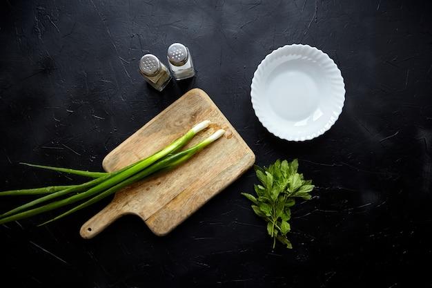 Planche à découper en bois et ingrédients d'herbes sur la table avec des feuilles de menthe fraîche et de l'oignon vert