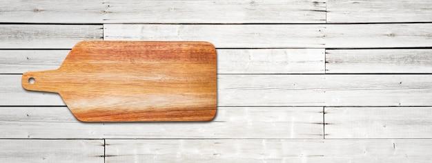 Planche à découper en bois isolée sur fond de bois blanc. bannière panoramique horizontale