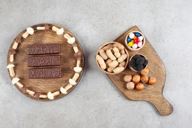 Une planche à découper en bois avec des noix et de la mûre.