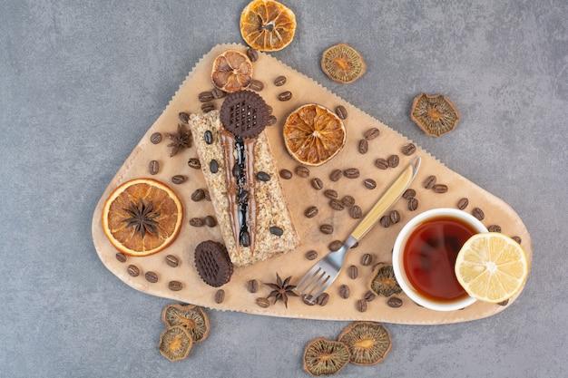 Une planche à découper en bois avec des oranges séchées et des grains de café.