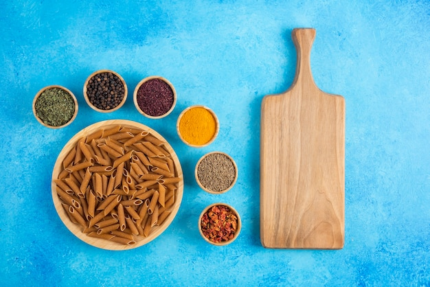 Planche à Découper En Bois Et Pâtes Brunes Crues Aux épices Sur Fond Bleu. Photo gratuit