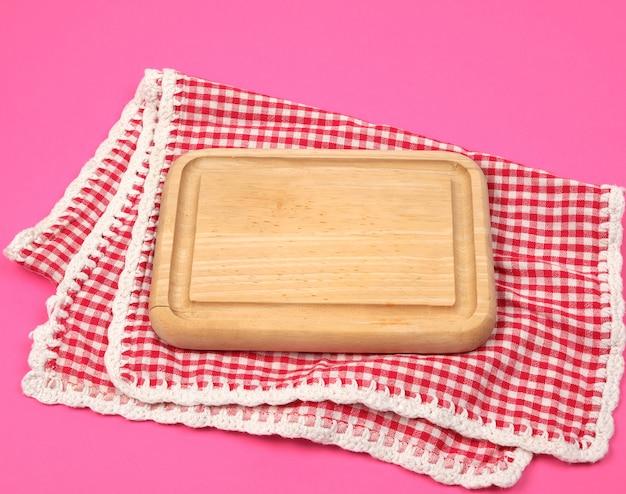 Planche à découper en bois de petite cuisine et serviette de cuisine à carreaux rouges blancs