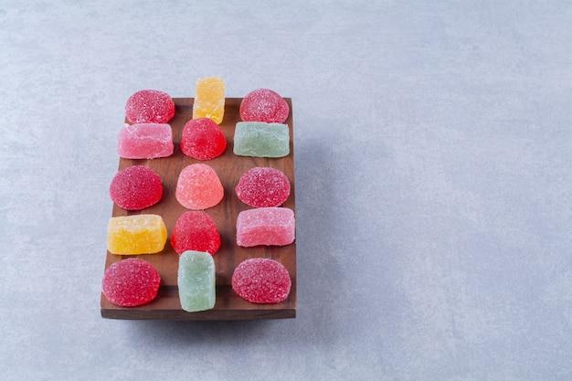 Une planche à découper en bois pleine de bonbons gélifiés sucrés colorés.