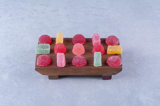 Une planche à découper en bois pleine de bonbons gélifiés sucrés colorés