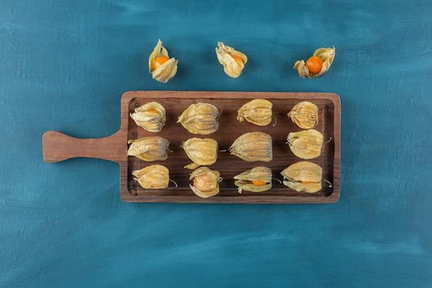 Une planche à découper en bois pleine de fruits secs cumquat.