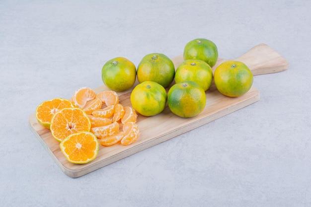 Planche à découper en bois pleine de mandarines aigres sur blanc