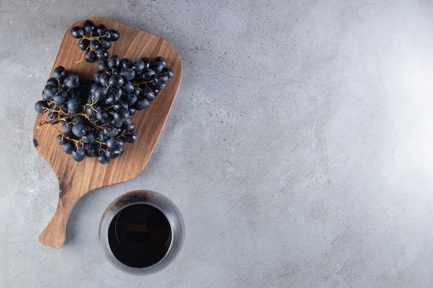 Une planche à découper en bois avec des raisins et une tasse de jus en verre.