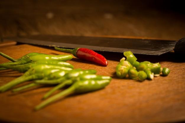 Planche à découper en bois rond. piments verts et rouges. couteau