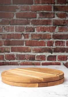 Planche à découper en bois ronde vide sur fond de mur de brique brune