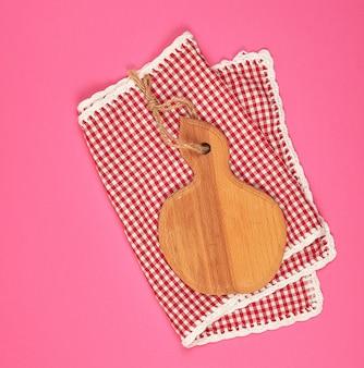 Planche à découper en bois et serviette de cuisine à carreaux rouge blanc