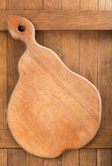 Planche à découper en bois sur la surface de la table en bois foncé