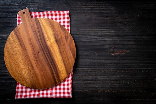 Planche à découper en bois vide avec un torchon