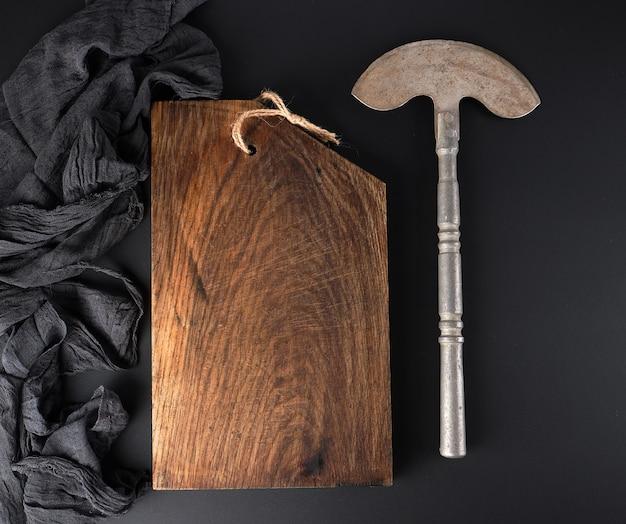 Planche à découper brune et vieille hachette en fer pour couper de la viande ou des légumes