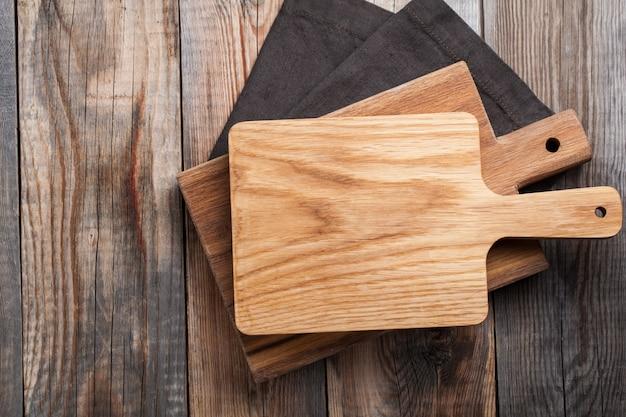 Planche à découper en chêne sur une serviette sur la table de cuisine en bois.