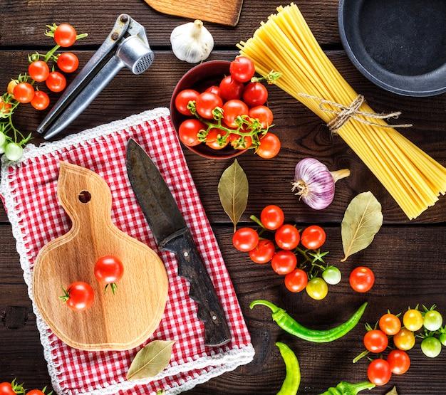 Planche à découper avec un couteau et tomates cerises rouges fraîches
