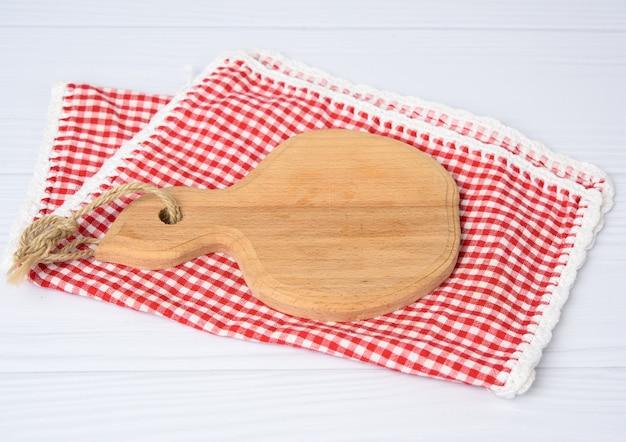 Planche à découper de cuisine en bois brun et serviette rouge sur une table blanche