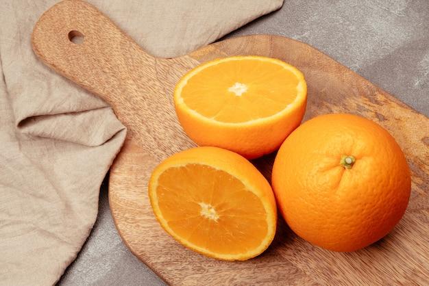 Planche à découper de cuisine en bois avec une orange coupée en deux et une orange entière