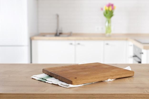 Planche à découper de cuisine sur le dessus de table de cuisine sur la cuisine flou
