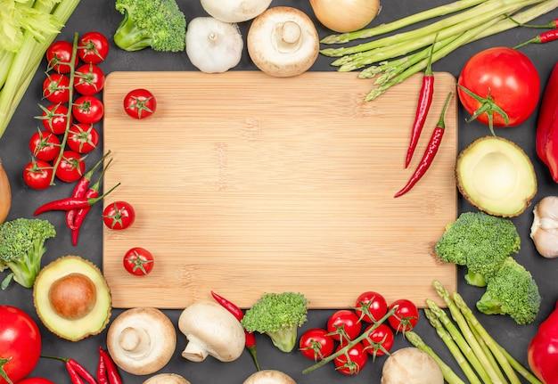 Planche à découper et divers légumes frais autour