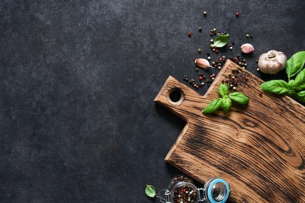 Planche à découper avec du basilic frais et des épices sur une table en béton noir. vue de dessus avec espace de copie.