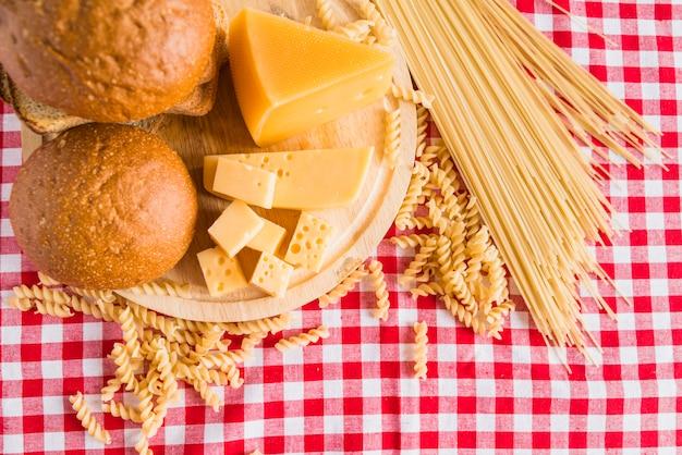 Planche à découper avec du fromage frais près du pain et des pâtes dispersées sur la table