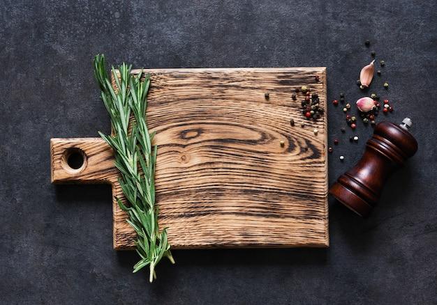 Planche à découper avec du romarin frais et des épices sur une table en béton noir. vue de dessus avec espace copie