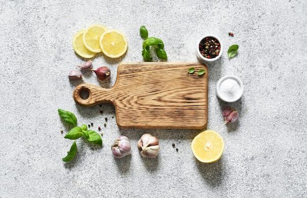 Planche à découper avec des épices et du citron sur un fond de béton clair