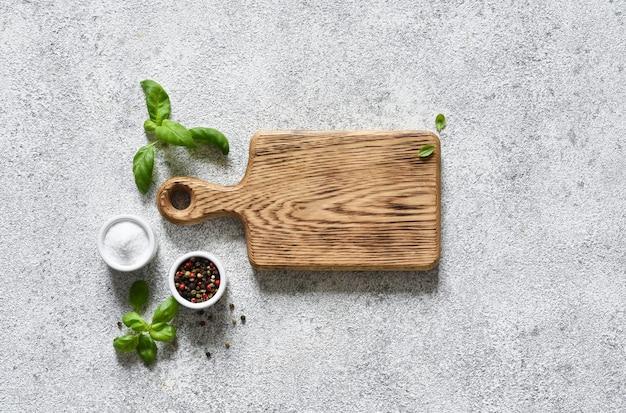 Planche à découper avec des épices sur un fond de béton clair