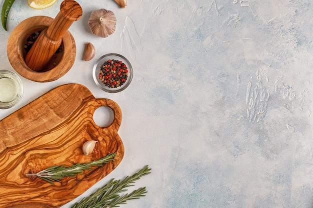 Planche à découper et épices pour cuisiner sur fond clair