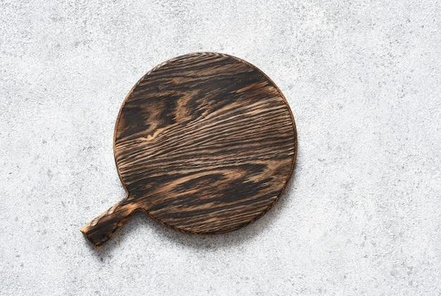Planche à découper sur un fond de béton clair.