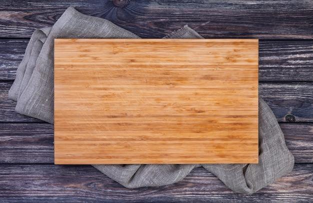 Planche à découper sur fond de bois foncé, vue de dessus