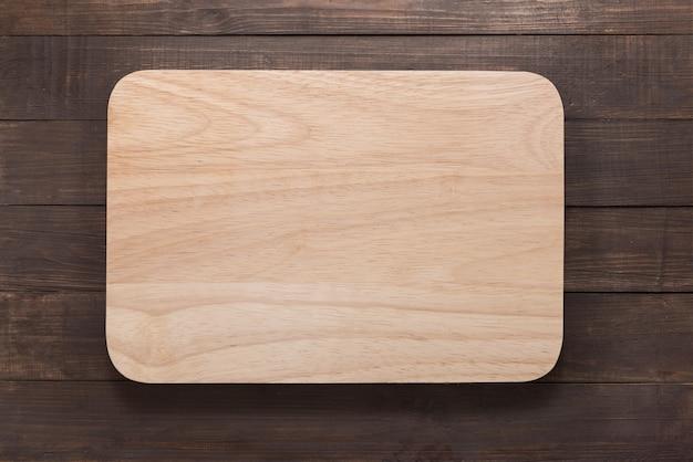 Planche à découper sur le fond en bois. vue de dessus