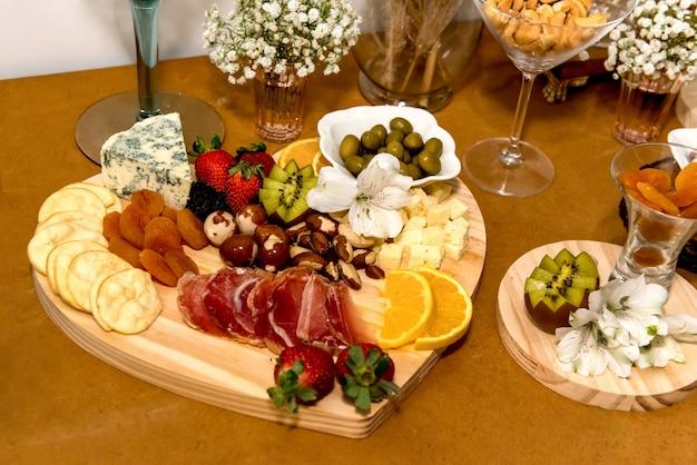 Planche à découper en forme de coeur avec nourriture, fromage, abricot, olive, salami, fraise et kiwi.